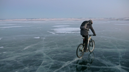 Man is riding a bicycle on ice. The cyclist is dressed in a gray down jacket, backpack and helmet. Ice of the frozen Lake Baikal. The tires on the bicycle are covered with special spikes. The traveler is ride a cycle.