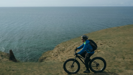 Fat bike also called fatbike or fat-tire bike in summer driving through the hills. The guy is riding a bike along the sand and grass high in the mountains. He performs some tricks and runs dangerously. In the distance, rocks and the sea can be seen. Banco de Imagens