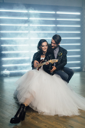 Wedding in the style of rock. Rocker or Biker wedding. Guys with stylish leather jackets. Its a rocknroll baby Sweet couple in a photo studio. Steep shooting with electric guitar and smoke.