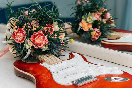 Wedding in the style of rock. Rocker or Biker wedding. Guys with stylish leather jackets. Its a rocknroll baby Wedding bouquet and electric guitar. Stock Photo