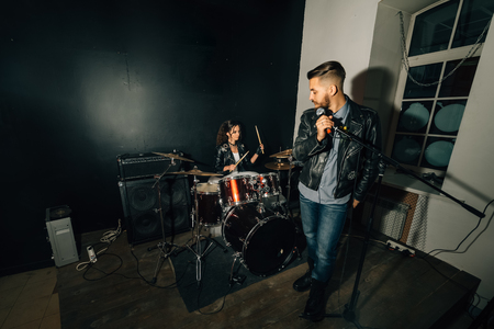Wedding in the style of rock. Guys with stylish leather jackets. Its a rocknroll baby Sweet couple in a music studio. The bride plays the drums, and the groom sings.