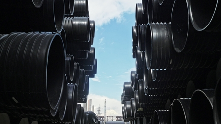 Warehouse of finished plastic pipes industrial outdoors storage site. Manufacture of plastic water pipes factory. Process of making plastic tubes on the machine tool with the use of water and air pressure.