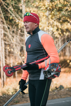 Training an athlete on the roller skaters. Biathlon ride on the roller skis with ski poles, in the helmet. Autumn workout. Roller sport. Adult man riding on skates. 스톡 콘텐츠