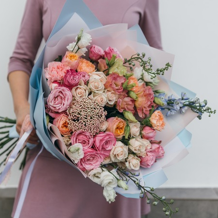 Colorful bouquet of different fresh flowers in the hands of a florist woman. Rustic flower background. Craft bouquet of flowers.
