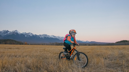 One caucasian children rides bike in wheat field. Little girl riding black orange cycle on background of beautiful snowy mountains. Biker motion ride with backpack and helmet. Mountain bike hardtail.