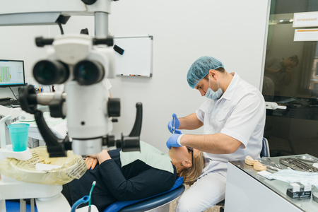 Doctor used microscope. Dentist is treating patient in modern dental office. Operation is carried out using cofferdam. Client is inserted and restored teeth, make denture. Orthodontist and assistant work in protective masks. Banco de Imagens