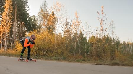 Training an athlete on the roller skaters. Biathlon ride on the roller skis with ski poles, in the helmet. Autumn workout. Roller sport. Adult man riding on skates. Reklamní fotografie