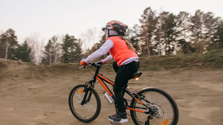 One caucasian children rides bike road track in dirt park. Girl riding black orange cycle in racetrack. Kid goes do bicycle sports. Biker motion ride with backpack and helmet. Mountain bike hardtail. 写真素材