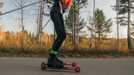 Training an athlete on the roller skaters. Biathlon ride on the roller skis with ski poles, in the helmet. Autumn workout. Roller sport. Adult man riding on skates. Stock Photo