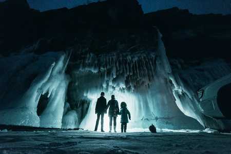 Surreal landscape with people exploring mysterious ice grotto cave. Outdoor adventure. Family exploring huge icy cave, dark majestic landscape. Magical silhouettes on background of illuminated ice blocks. Mysterious and strange magic light.