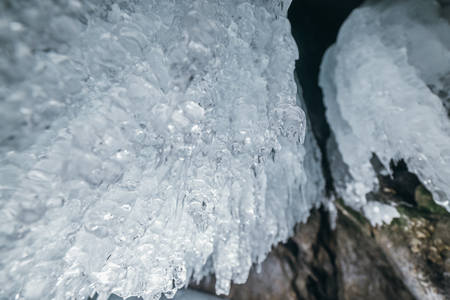 Winter Baikal. Olkhon Island. Ice grotto. Thick blue ice and icicles on the coastal rocks of Olkhon Island in winter. Natural cold background. The winter the lake and the surrounding area becomes ice.