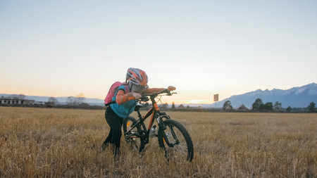 One caucasian children walk with bike in wheat field. Little girl walking black orange cycle on background of beautiful snowy mountains. Biker stand with backpack and helmet. Mountain bike hardtail. Stock Photo