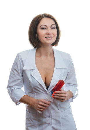 Sexually doctor woman on isolated white background. Caucasian woman medic with beautiful sexy pantyhose, bra and panties. The girl has a big syringe with a red liquid. 免版税图像