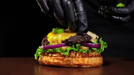 Craft burger is cooking on black background. Consist: red sauce salsa, lettuce, red onion, pickle, cheese, chilli green pepper, air bun and marbled meat beef. Not made ideal. Loving hand made.