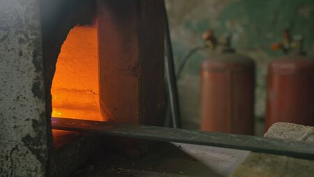 Forge workshop. Smithy manual production. Gas furnace for heating metal. Modern melting stove for iron steel. The blacksmith makes iron products for manufacture of fireplaces, stoves. Cinematic look.
