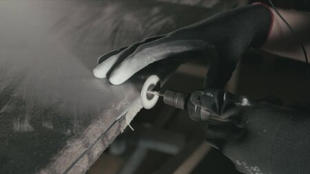 Forge. Smithy. Glass cutting and processing for fireplace doors. Circular glass cutter. Worker cut glass with glass cutting diamond. Polish an angle grinder with an abrasive circular disk nozzle. Stock fotó