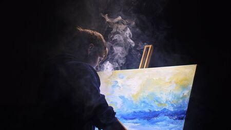 Artista copista pintar paisaje marino con barco en el océano. Vaper smoke vape e-cigarrillo. Decorador artesano dibuja como un barco navega en un mar azul con óleo acrílico. Dibuja el dedo, el pincel, la paleta de cuchillos. Interior.