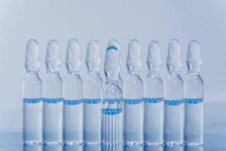 Medizinische Ampulle aus Glas zur Injektion. Das Medikament ist das flüssige Natriumchlorid mit der wässrigen Lösung in der Ampulle. Nahaufnahme. Flaschen Ampulle mehrfarbig auf Hintergrundfarbe und Wasser. Menschliches Plasma.