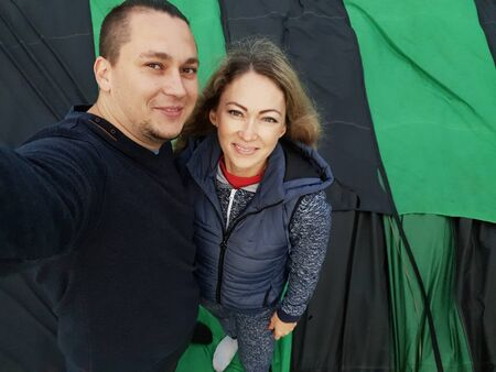 Adventure love couple on hot air balloon watermelon. Man and woman kiss hug love each other. Burner directing flame into envelope. Fly in morning blue sky. Happy people take selfie in hot air ballon. Stock fotó