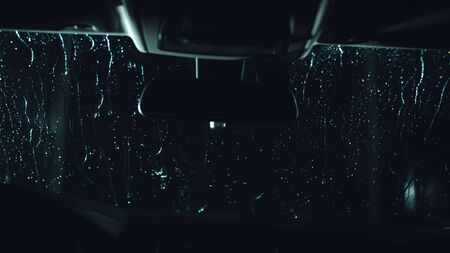 Drops flow down the windscreen. Inside view of a windshield car. Dark black cinematic picture. Process stage of polishing and washing a auto. Movement zoom camera dolly shooting platform.