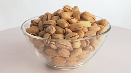 Nuts pistache rotate are on a table in a plate. Snack in transparent dish on an isolated white background are spinning moving. Delicious and healthy protein-rich diet food.