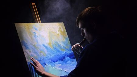 Artist copyist paint seascape with ship in ocean. Vaper smoke vape e-cigarette. Craftsman decorator draw as boat sail on blue sea with acrylic oil color. Draw finger, brush, knife palette. Indoor.