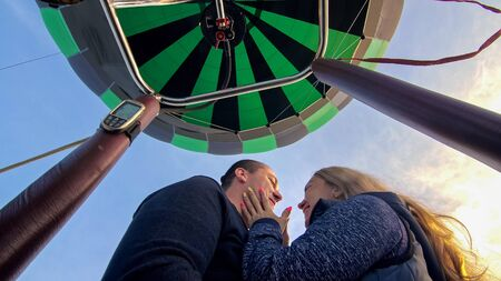 Adventure love couple on hot air balloon watermelon. Man and woman kiss hug love each other. Burner directing flame into envelope. Fly in morning blue sky. Happy people take selfie in hot air ballon. Stock Photo