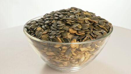 Nuts peeled pumpkin seed rotate are on a table in a plate. Snack in transparent dish on an isolated white background are spinning moving. Delicious and healthy protein-rich diet food.