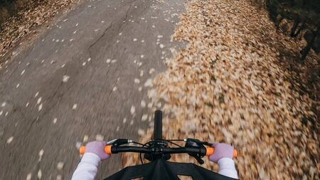 Pov view. One caucasian children rides bike road in autumn park. Little girl riding black orange mtb cycle in forest. Kid goes do bicycle sports. Biker motion ride with backpack and helmet.