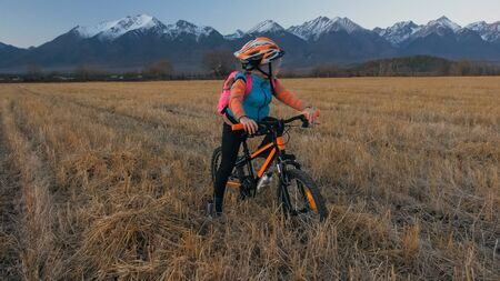 One caucasian children walk with bike in wheat field. Little girl walking black orange cycle on background of beautiful snowy mountains. Biker stand with backpack and helmet. Mountain bike hardtail. 版權商用圖片
