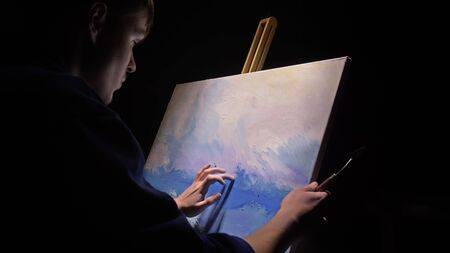 Artist copyist paint seascape with ship in ocean. Craftsman decorator draw as boat sail on blue sea with acrylic oil color. Draw finger, brush, knife palette. Canvas, easel in studio, indoor.