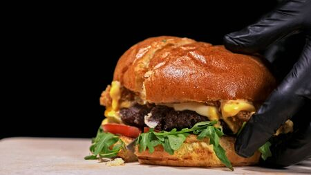 Cut craft burger is cooking on black background in black food gloves. Consist: sauce, arugula, tomato, red onion rings fries, cucumber, cheese, air bun and marble meat beef. Not made ideal. Looks real, loving hand made. Stock fotó