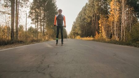 Training an athlete on the roller skaters. Biathlon ride on the roller skis with ski poles, in the helmet. Autumn workout. Roller sport. Adult man riding on skates. Zdjęcie Seryjne