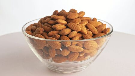 Nuts almond rotate are on a table in a plate. Snack in transparent dish on an isolated white background are spinning moving. Delicious and healthy protein-rich diet food.