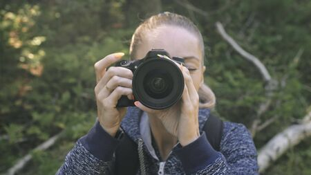 Traveler photographing scenic view in forest. One caucasian woman shooting close up look. Girl take photo video on dslr mirrorless camera. Professional photographer travel with backpack. Outdoor.