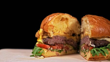 Cut craft burger is cooking on black background in black food gloves. Consist: sauce, arugula, tomato, red onion rings fries, cucumber, cheese, air bun and marble meat beef. Not made ideal. Looks real, loving hand made. Imagens