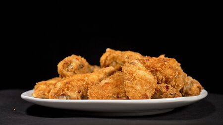Cool beautiful fresh juicy cooked chicken wings in breading. Buffalo wings spread on food white plate in table. Very tasty and beautiful. Cooking with deep fryer fry machine. Reklamní fotografie