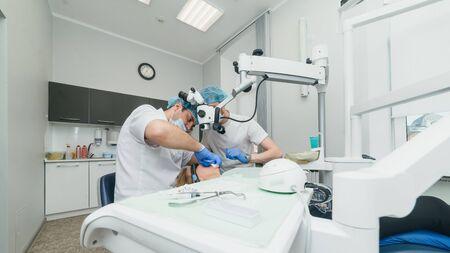 Lekarz używany mikroskop. Dentysta leczy pacjenta w nowoczesnym gabinecie stomatologicznym. Operacja odbywa się za pomocą koferdamu. Klient wstawia i odbudowuje zęby, wykonuje protezę. Ortodonta i asystent pracują w maskach ochronnych. Zdjęcie Seryjne