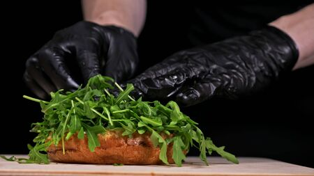 Craft burger is cooking on black background. Consist: sauce, arugula, tomato, red onion, bacon, red currant sauce, ricotta cottage fresh cheese, air bun and marble meat beef. Not made ideal. Looks real, loving hand made. Stockfoto
