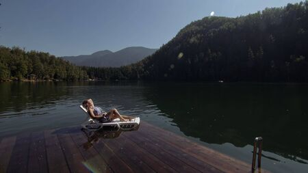 Woman lie on a sunbed in sunglasses and a boho silk shawl. Girl rest on a flood wood underwater pier. The pavement is covered with water in the lake. In the background are mountain and a forest. Stok Fotoğraf