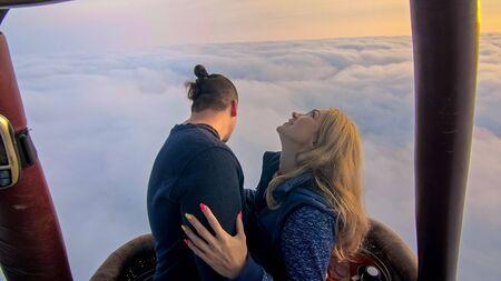 熱気球スイカの冒険愛のカップル。男女のキスは、お互いに愛し合う抱擁。火炎を封筒に向けるバーナー。朝の青空で飛ぶ。幸せな人々は熱い空気のバロンで自分撮りを取る。