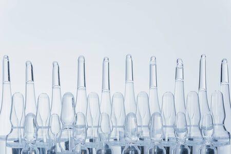 Medizinische Ampulle aus Glas zur Injektion. Das Medikament ist ein trockenes weißes Pulver des Präparates Penicillin oder eine Flüssigkeit mit einer wässrigen Lösung in einer Ampulle. Nahaufnahme. Flaschenampulle mit Aluminiumkappe auf grauem Hintergrund.
