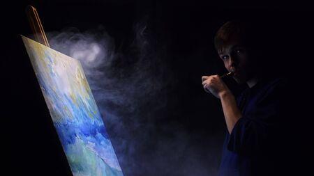 Un artiste copiste peint un paysage marin avec un navire dans l'océan. Vaper fume la vape e-cigarette. Un décorateur artisan dessine comme un bateau naviguant sur une mer bleue avec une couleur à l'huile acrylique. Dessinez le doigt, le pinceau, la palette de couteaux. Intérieur.