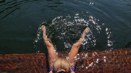 Woman sit on a pier in sunglasses and swimming suit. Girl rest on a flood wood underwater pier. The pavement is covered with water in lake. Lady in the water and splashes feet. View from above.