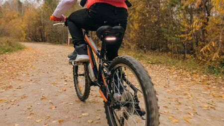 One caucasian children rides bike road in autumn park. Little girl riding black orange cycle in forest. Kid goes do bicycle sports. Biker motion ride with backpack and helmet. Mountain bike hardtail.