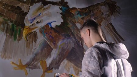 Artist designer draws an eagle on wall. Craftsman decorator paints picture with acrylic oil color looking at sketch in phone. Painter painter dressed in paint coat. Indoor. Dark magic cinematic look. 免版税图像