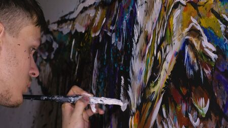 Artist designer draws an eagle on the wall. Craftsman decorator paints a picture with acrylic oil color. Painter painter dressed in a paint coat. Indoor. Dark magic cinematic look.