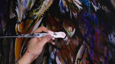 Artista diseñador dibuja un águila en la pared. El decorador artesano pinta un cuadro con pincel acrílico para óleo. Mirada cinematográfica de magia oscura de primer plano. Pintor vestido con una capa de pintura. Interior. Foto de archivo