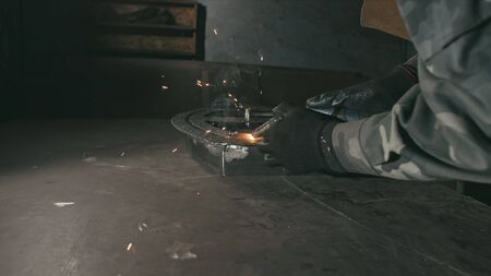 Forge workshop. Smithy. Worker in a welding hood helmet welds a part by electric welding. Sparks are reflected in the protective screen. Blacksmith makes iron product for manufacture. Slow motion.