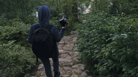 Traveler photographing scenic view in forest. One caucasian woman shooting nice magic look. Girl take photo video on dslr mirrorless camera. Professional photographer travel with backpack. Outdoor.